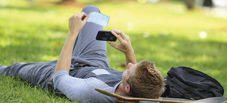 Man laying in the grass on his skateboard while taking a picture of a check using his mobile device