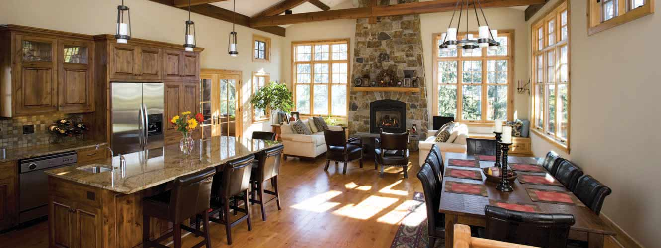 Image of a spacious kitchen with a stone fireplace and large dining room table